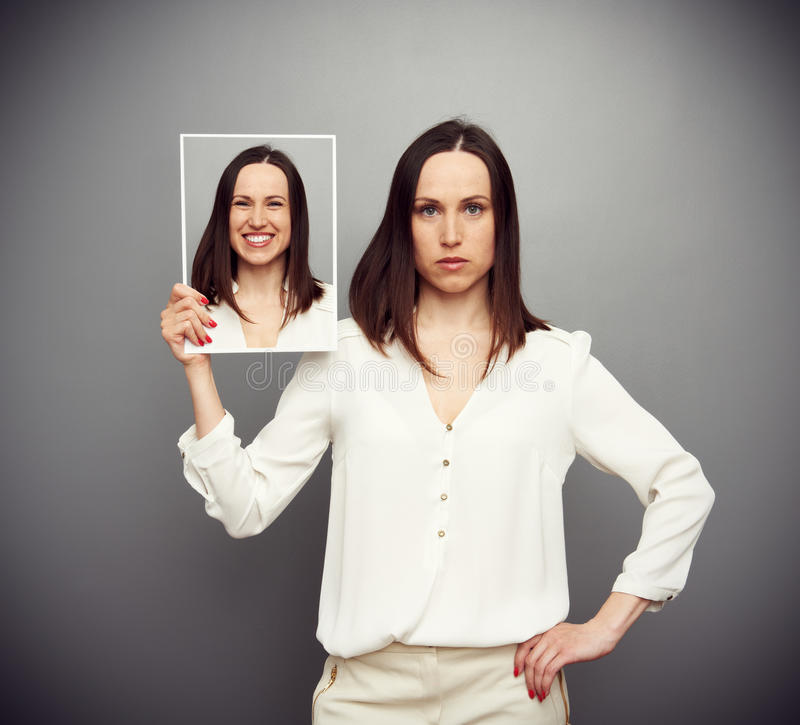 Unemotional woman hiding her gladness. Concept photo over dark background stock image