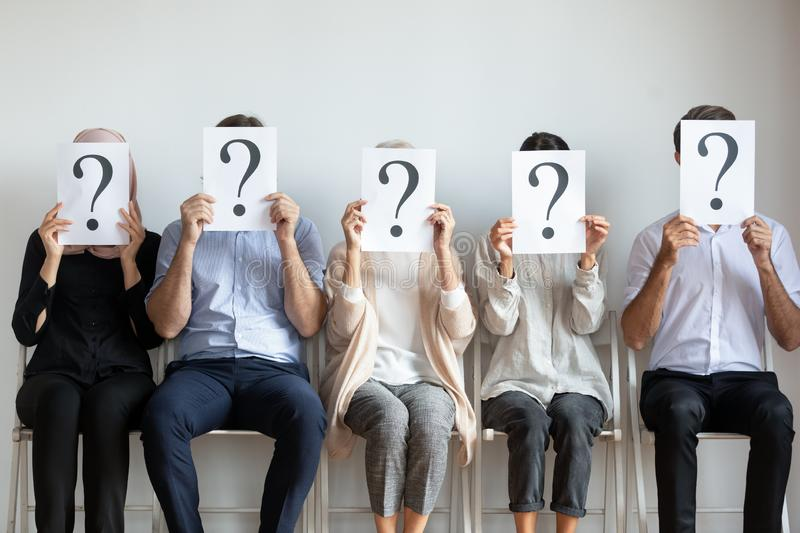 Unemployed businesspeople hiding face with questions waiting for job interview royalty free stock image