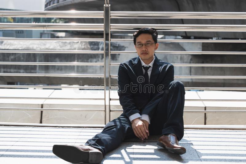 Unemployed stressed young Asian business man sitting on floor outdoors. Failure and layoff concept stock photography