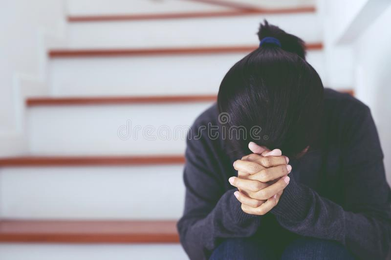 Unemployed women sad crisis despair and stress people compression sitting in house stairs feel stressful installment payment expen. Ses home depression situation royalty free stock photography