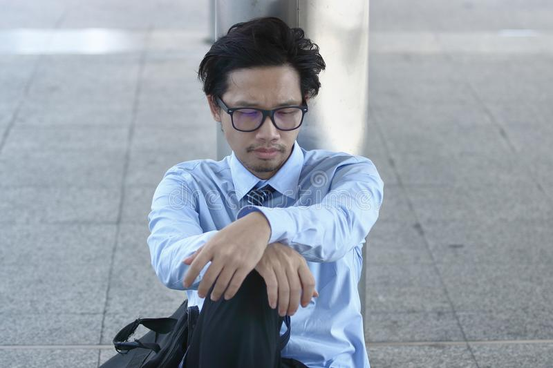 Unemployed young Asian businessman sitting on the floor of sidewalk office. Depressed unemployment business concept. stock photography