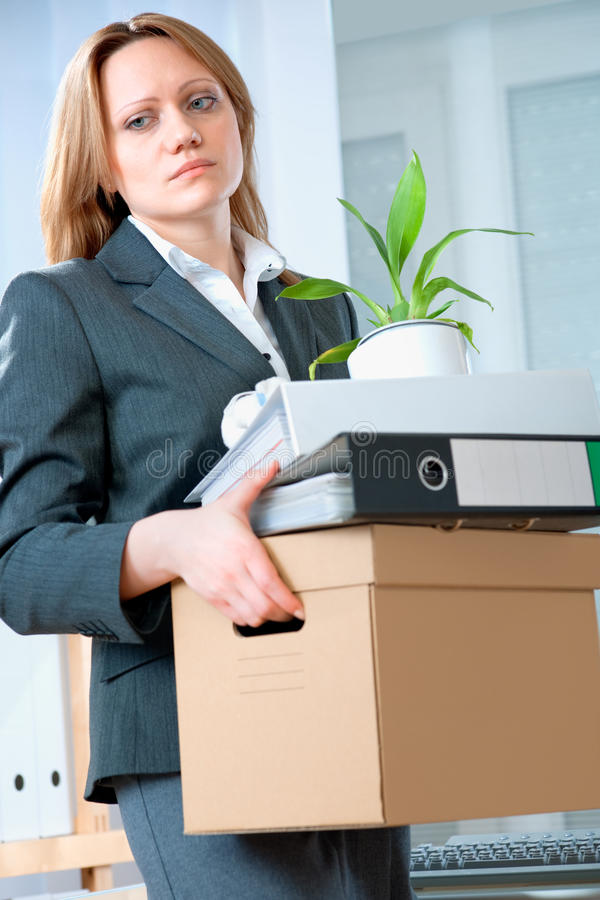 Unemployment concept. A fired woman in a suit carrying a box of personal items royalty free stock image