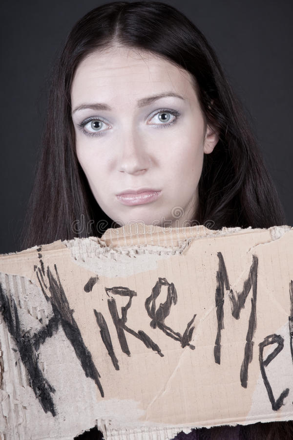 Unemployment. Young girl holds a cardboard sign. focus on eyes stock images