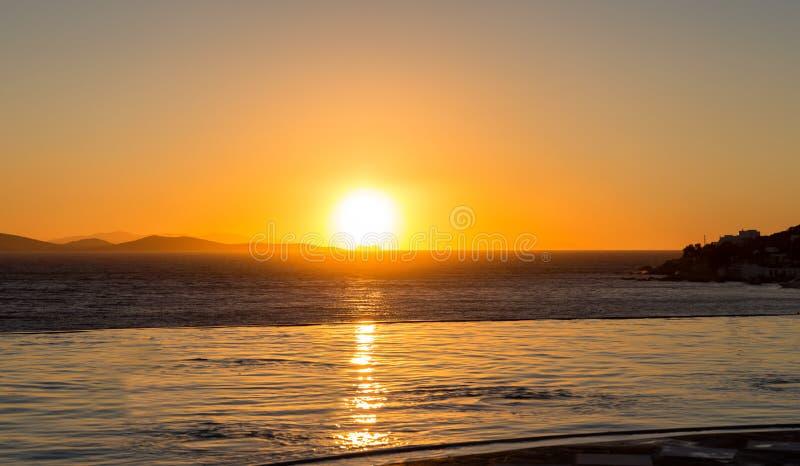 Unendlichkeitspool bei goldenem Sonnenuntergang stockbild
