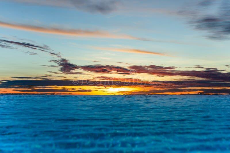 UnendlichkeitsSwimmingpool mit Sonnenunterganghimmel vover der Ozean lizenzfreie stockfotografie