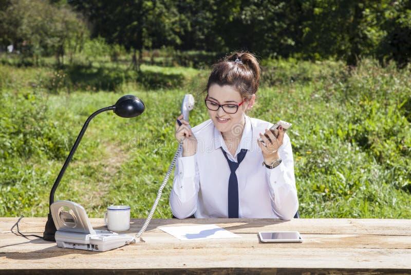 Unentschiedene Geschäftsfrau weiß nicht, welches Telefon, zum aufzuheben lizenzfreie stockfotografie