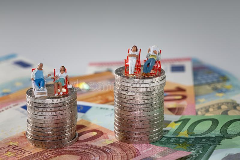 Unequal wealth. Couples with unequal wealth on euro coins stock images