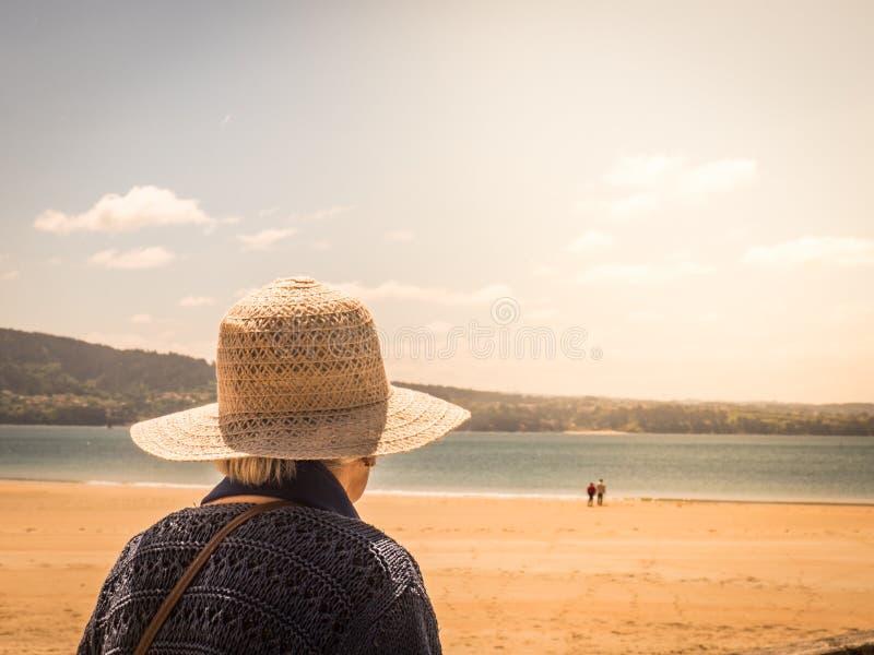 Unerkennbare alte Frau, die ein Paar in einem Strand betrachtet stockfotografie