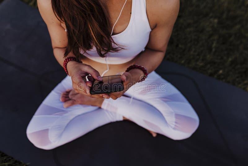 unerkennbare asiatische Frau entspannt nach ihrer Yogapraxis, die Musik an den Kopfhörern und am Handy hört Yoga und gesundes Leb stockbild