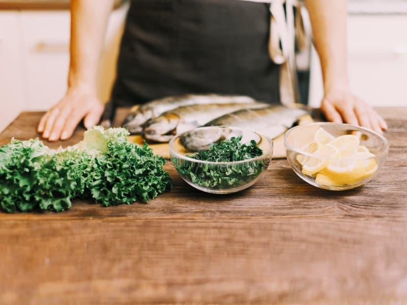 Unerkennbare Frau, die Fische in der Küche kocht lizenzfreie stockbilder