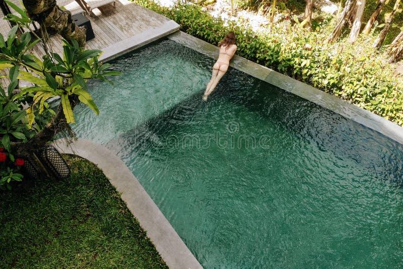 Unerkennbare Frau im beige Bikini, der im Unendlichkeitspool in Bali sich entspannt, bewundert eine schöne Ansicht der Palmen lux stockfotos