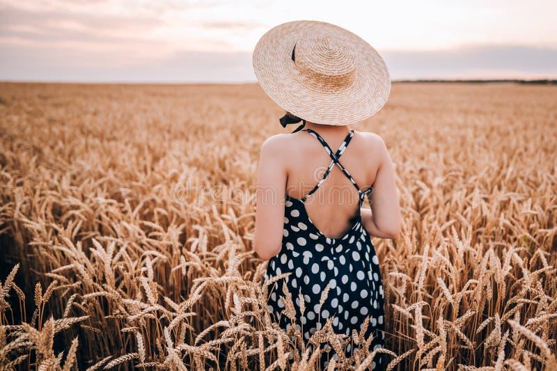 Unerkennbare Frau im Retrostilkleid und -hut, die auf dem goldenen Gebiet des Weizens aufwerfen stockfotos