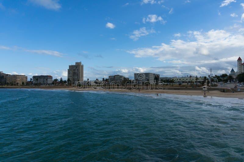 Unerkennbare Leute, die auf dem Strand in Port Elizabeth, Südafrika sich entspannen lizenzfreie stockfotos