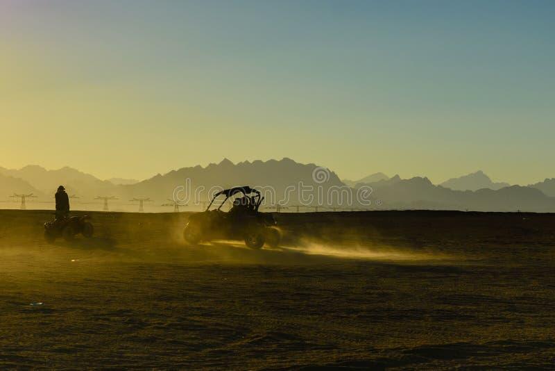 Unerkennbare Leute, die Buggy w?hrend der Safarireise bei Sonnenuntergang in der arabischen W?ste unweit von der Hurghada-Stadt,  lizenzfreie stockbilder