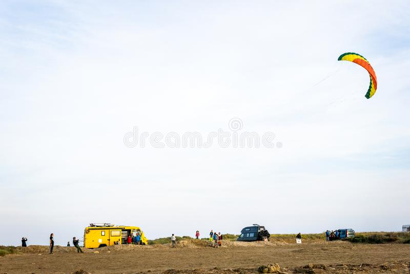 Unerkennbare Leute, die einen Brandungsdrachen auf dem Strand mit Packwagen im Hintergrund fliegen stockbild