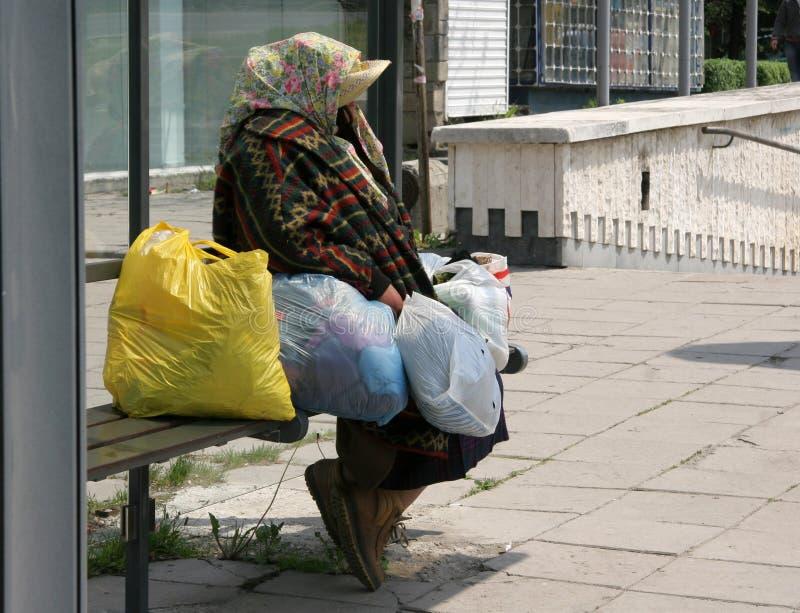 Unerkennbare obdachlose Frau sitzen auf einer Bushaltestelle Obdachloser Person im Bedarf Hungrige Leute Arme Person lizenzfreie stockfotografie