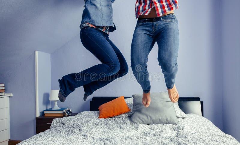 Unerkennbare Paare, die auf das Bett springen stockfotos