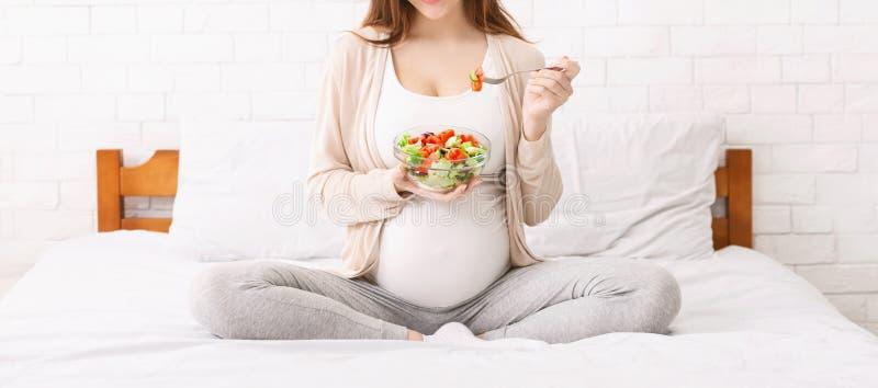 Unerkennbare schwangere Frau, die Gemüsesalat im Bett isst lizenzfreie stockfotografie