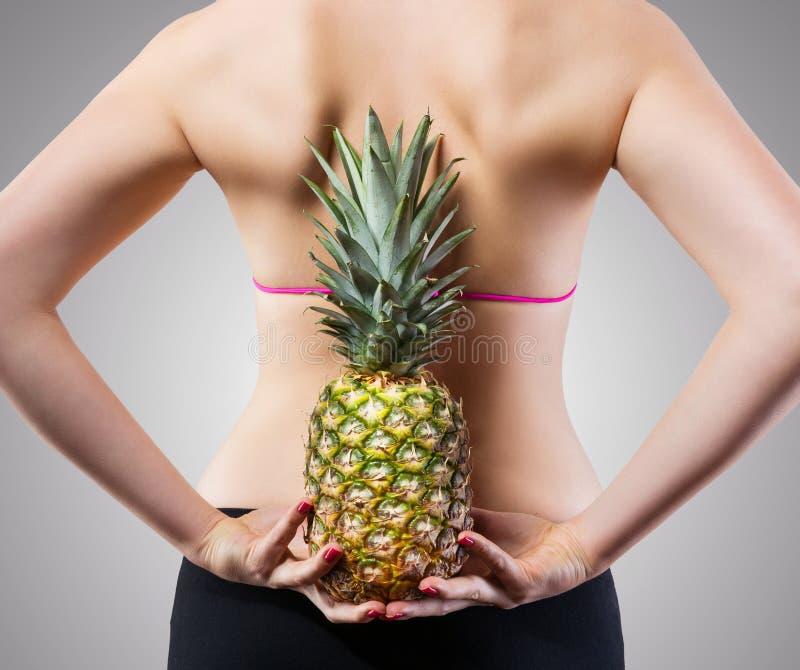 Unerkennbare Sitzfrau mit Ananas lizenzfreie stockfotografie