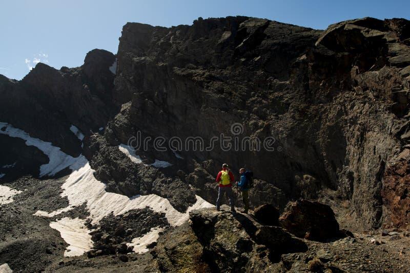 Unerkennbare Touristen, die auf Felsen stehen stockfotografie