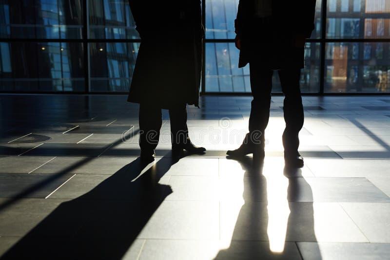 Unerkennbare Wirtschaftler, die in der Büro-Lobby stehen lizenzfreie stockfotos