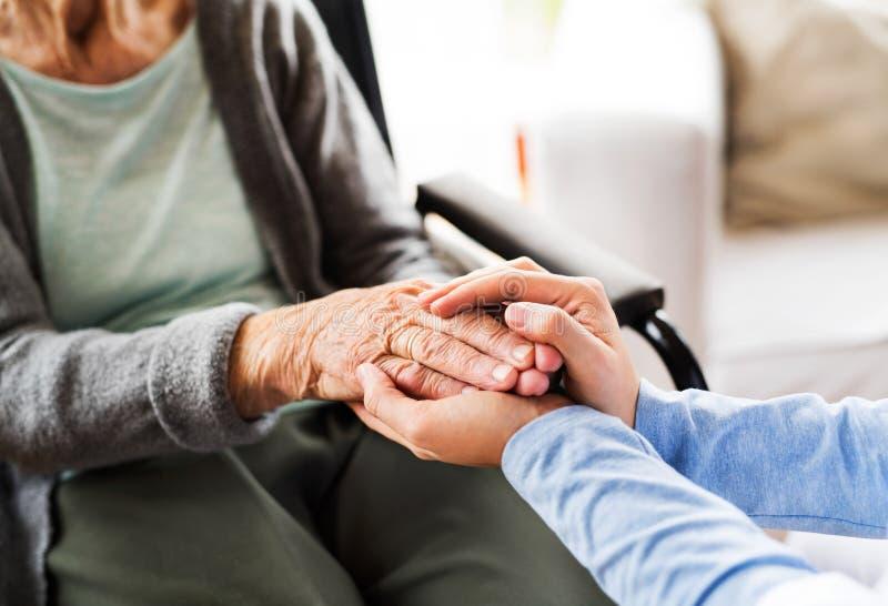 Unerkennbarer Gesundheitsbesucher und eine ältere Frau während der Hauptkraft lizenzfreie stockbilder