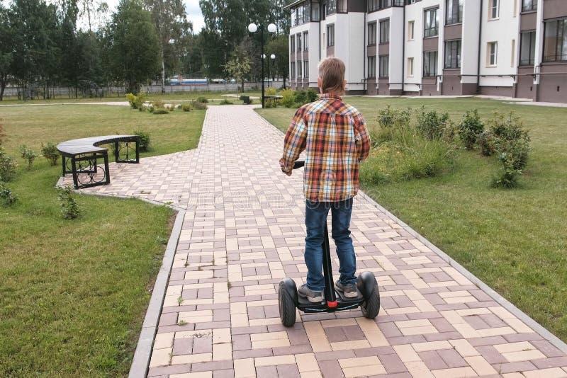 Unerkennbarer Junge rollt auf Kreiselkompassroller nahe dem Haus Rückseitige Ansicht lizenzfreie stockbilder