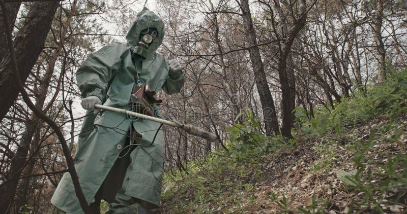 Unerkennbarer Kerl des niedrigen Winkels in hazmat Klage und Gasmaske, die nach Strahlung mit Geigerzähler in verlassenem Wald su stockbild