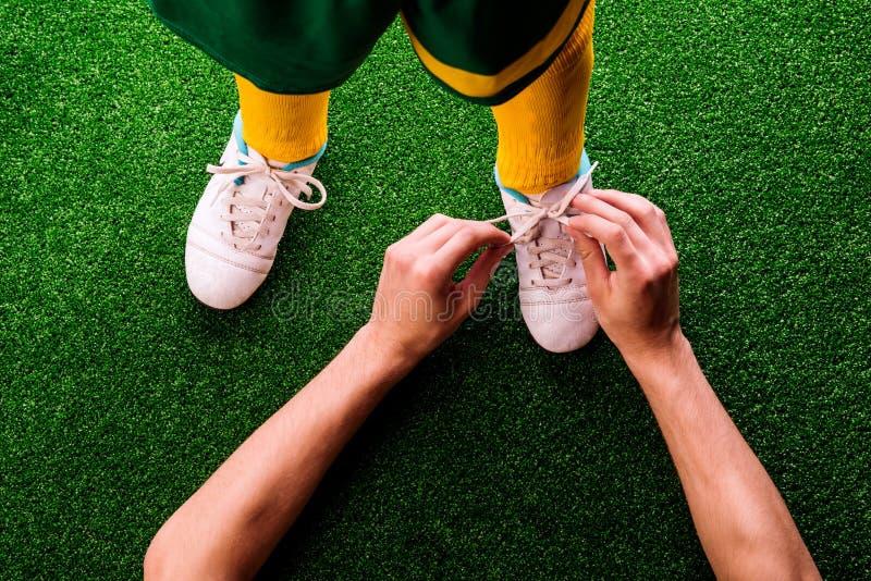 Unerkennbarer Vater, der Spitzee an seinem Sohn, Fußball bindet lizenzfreies stockbild