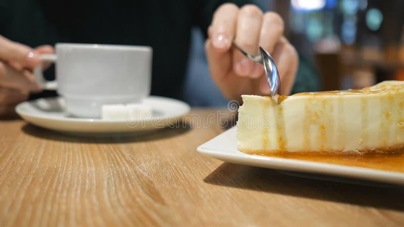 Unerkennbares junges Mädchen, das Kuchen am Café isst stockfotografie
