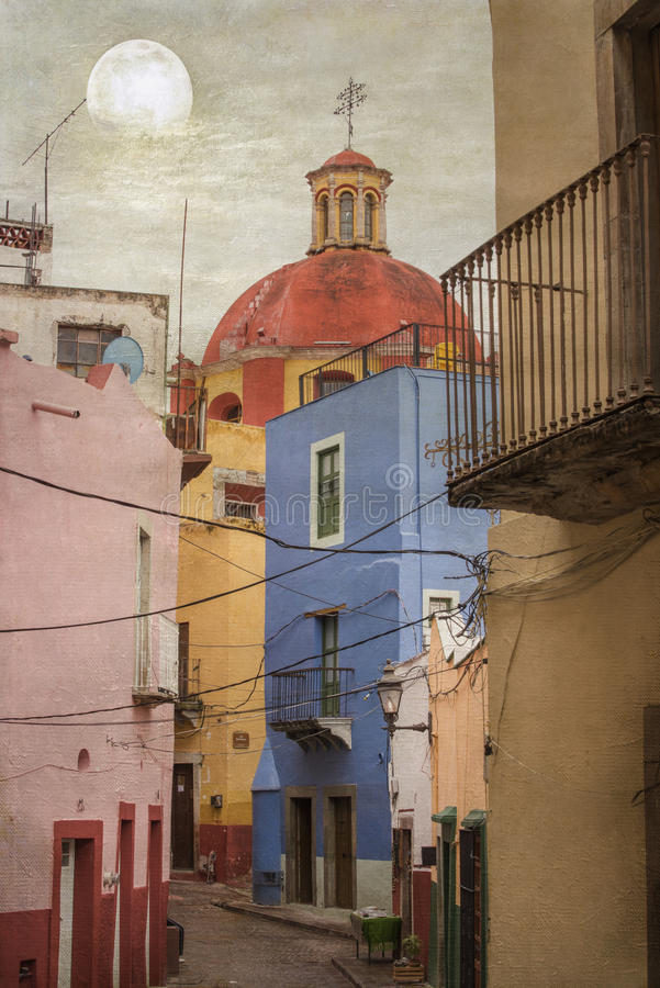 UNESCO World Heritage city of Guanajuato, Mexico. Narrow street filled with colorful buildings and church dome in background with texture applied royalty free stock photo