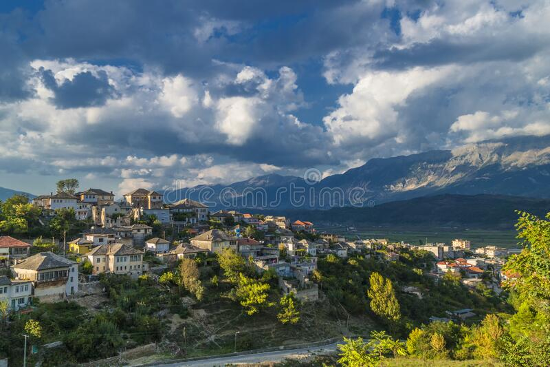 Unescos historiska skyddade stad Gjirocaster , södra Albanien mot bakgrund av Balkanbergen och ett dramatiskt molnigt luftrum Hou royaltyfri foto