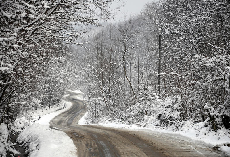 Uneven curved road through snowy forest. In cloudy winter day royalty free stock image