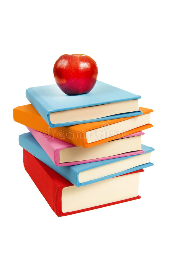 Uneven Stack Of Books With Red Apple. Concept that reading is healthy for you. Vertical shot of an uneven stack of bright colored covered books. Lots of copy stock photo