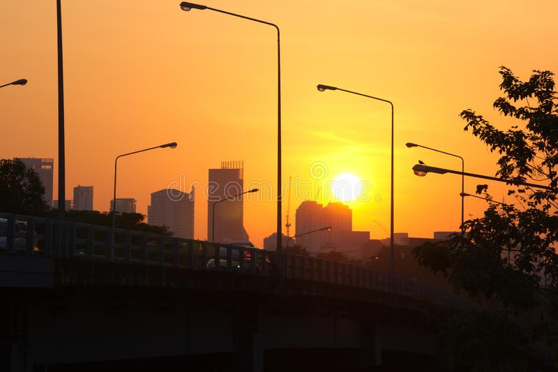 A colorful sunrise of orange and yellow hues, over the dark silhouette of a bridge in Bangkok, Thailand. An unexpected, majestic, colorful sunrise of orange and royalty free stock photo
