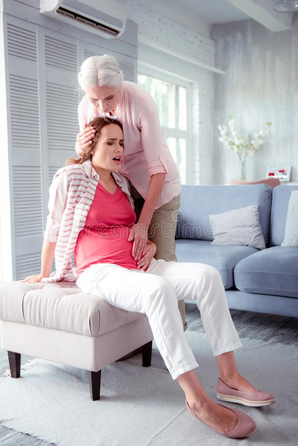 Pregnant young woman feeling some unexpected pain at home. Unexpected pain. Pregnant young women wearing white trousers feeling some unexpected pain at home stock photography