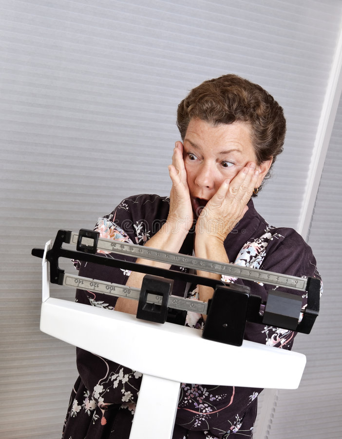 Unexpected Weight Gain. Pretty mature woman in a kimono weighing herself on a medical scale, looking shocked at her sudden weight gain royalty free stock photos