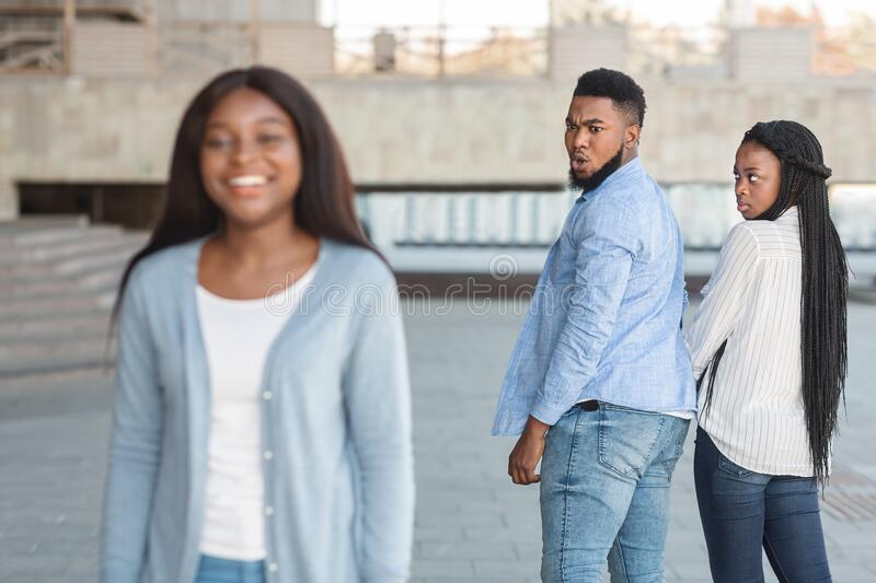 Unfaithful guy staring at another woman while walking with girlfriend outdoors. Womanizer concept. Unfaithful black guy turning and staring at another women royalty free stock photos