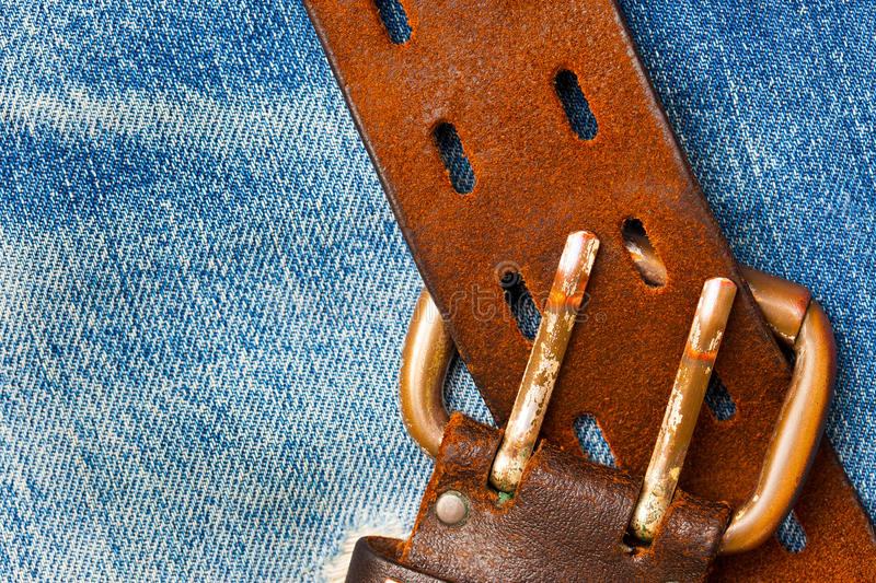 Unfastened old leather belt with vintage buckles. On the jeans background stock image