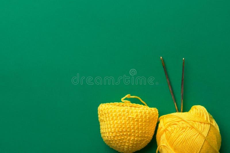 Unfertige Näharbeit von der gelben Rohbaumwollegarn-Schnäppchenhäkelarbeit auf dunkelgrünem Hintergrund Strickende handgemachte K lizenzfreie stockbilder