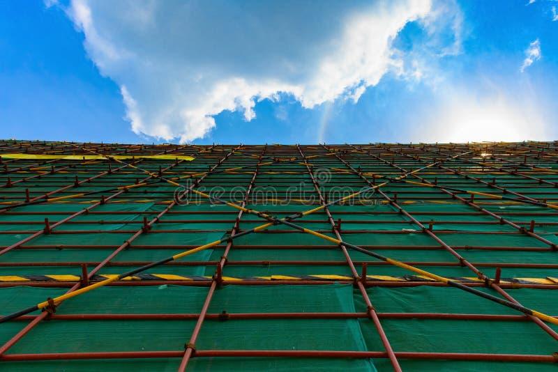 unfiinshed在天空蔚蓝下的大厦和网的外部与保护脚手架的 免版税库存图片