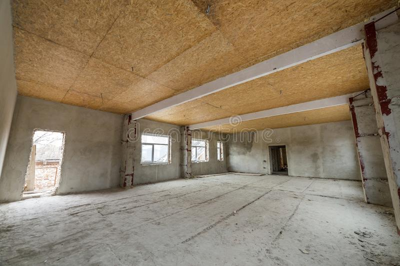 Unfinished apartment or house big loft room under reconstruction. Plywood ceiling, plastered walls, window openings, cement floor royalty free stock photos