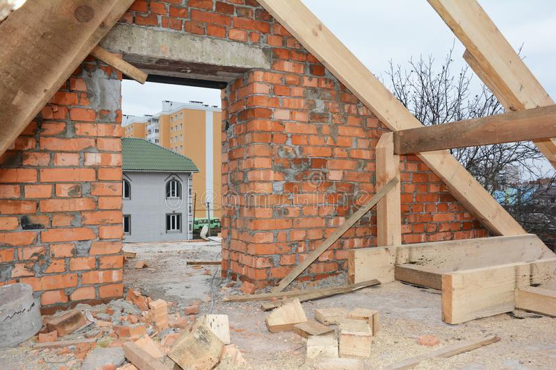 Unfinished attic house rooftop roofing construction with trusses, wooden beams, eaves, timber.  Attic house roof wooden frame royalty free stock photo