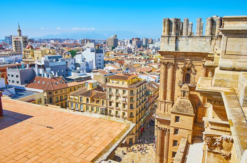Unfinished bell tower of Malaga Cathedral, Spain. Malaga Cathedral roof observes unfinished stone right bell tower, rising over the city roofs, Andalusia, Spain royalty free stock images