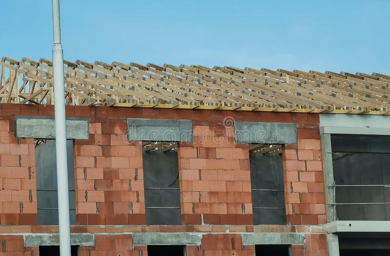 Unfinished brick house, building under construction and wooden roof frame stock photography