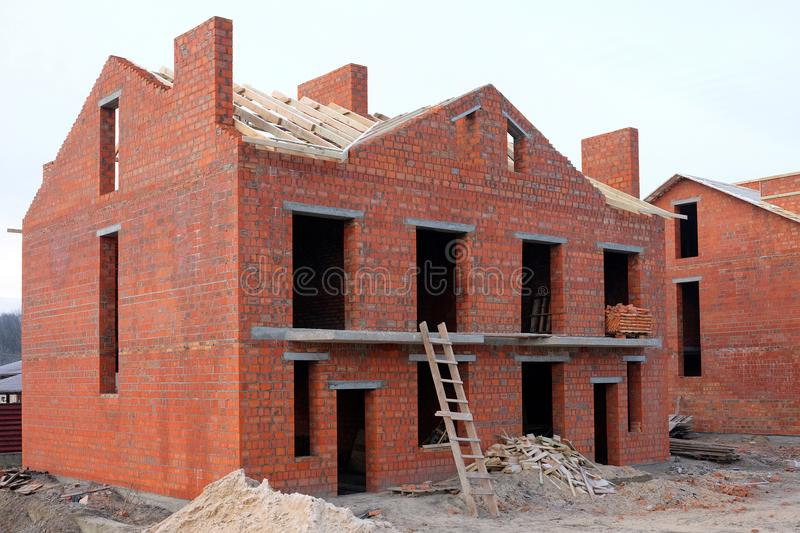 Unfinished brick house construction, still under construction. Unfinished roof under construction royalty free stock photo