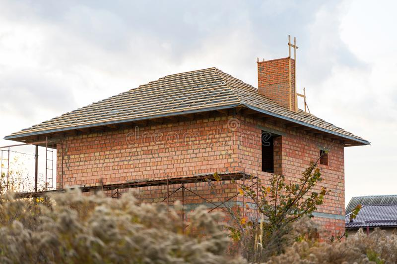 An unfinished brick house with a wooden roof frame is still under construction. royalty free stock photography