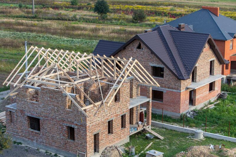 Unfinished brick house with wooden roof structure under construction stock image