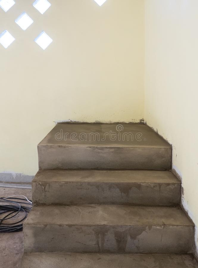 Unfinished cement staircase near the soft yellow wall. stock image