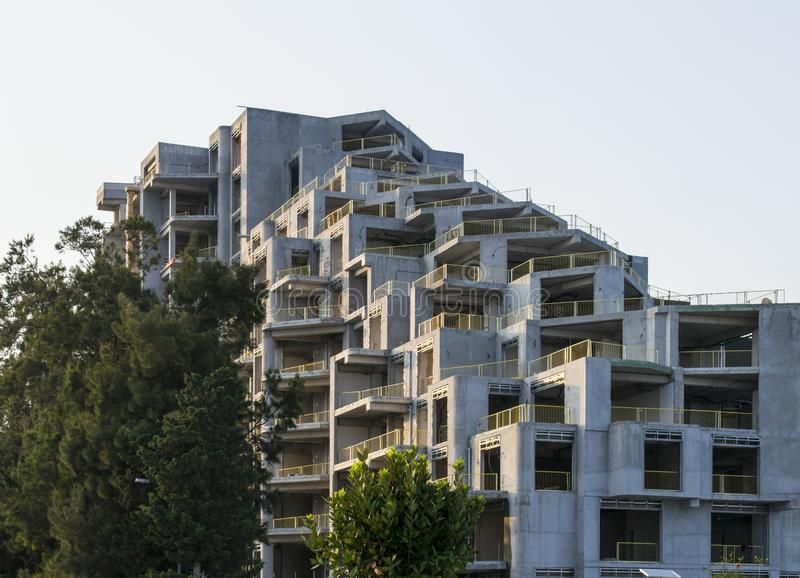 Unfinished construction. Work in progress high-rise house with grey facade. royalty free stock images